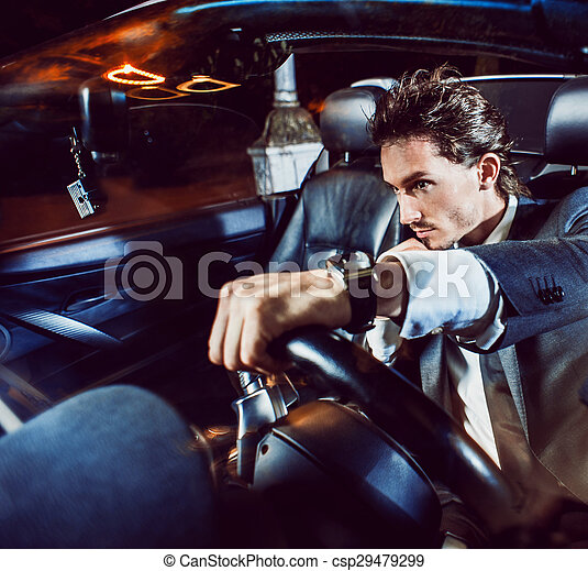 Un hombre apuesto con barba en un auto de traje - csp29479299