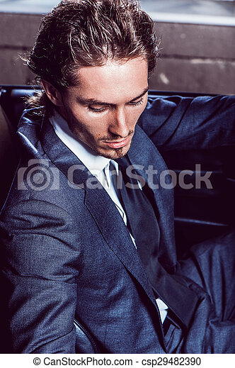 Un hombre apuesto con barba en un auto de traje - csp29482390