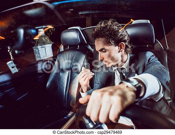 Un hombre apuesto con barba en un auto de traje - csp29479469