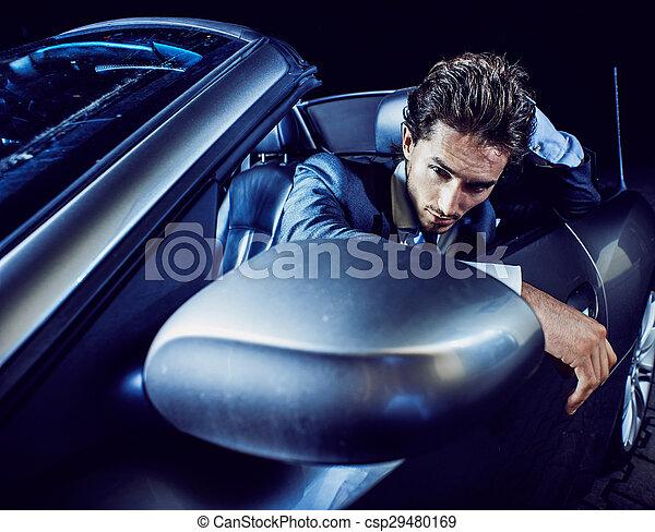 Un hombre apuesto con barba en un auto de traje - csp29480169