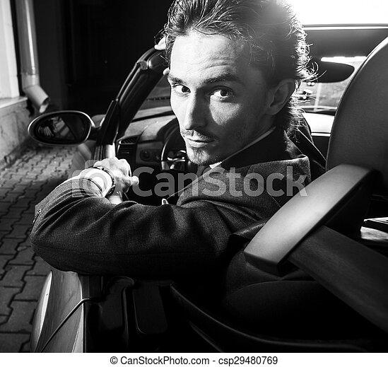 Un hombre apuesto con barba en un auto de traje - csp29480769
