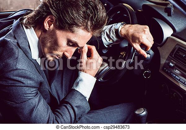 Un hombre apuesto con barba en un auto de traje - csp29483673