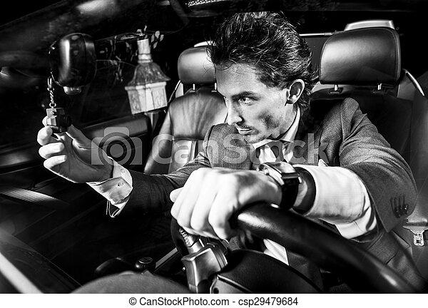Un hombre apuesto con barba en un auto de traje - csp29479684