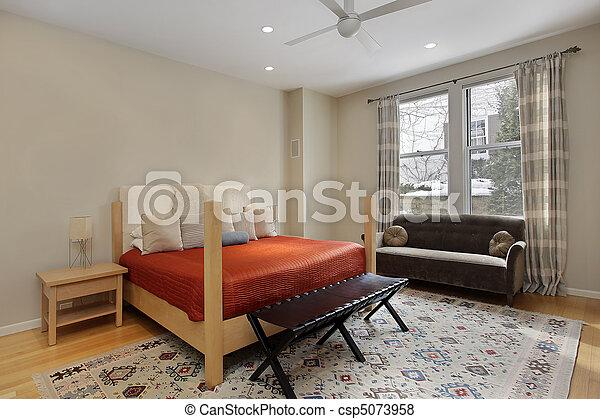 Guest bedroom with orange bedspread - csp5073958