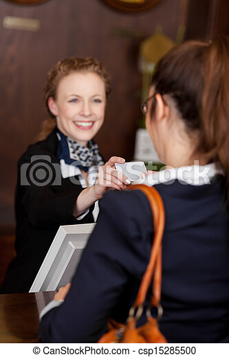 Guest receiving a business card at reception - csp15285500