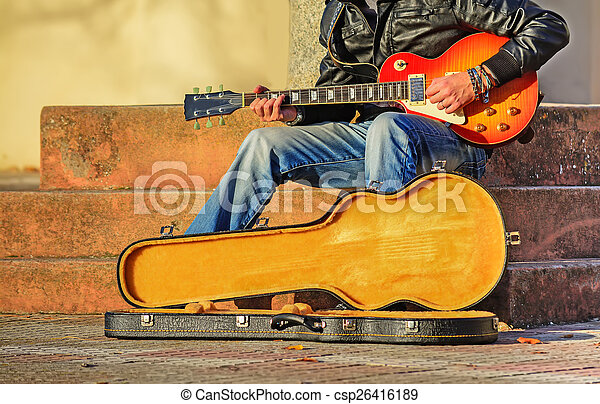 guitar player with open guitar case - csp26416189