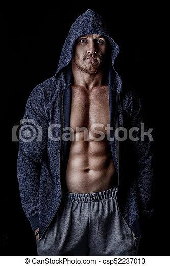 Guy in hoodie. Handsome athletic man in hoodie posing over black ... 49b9a897d