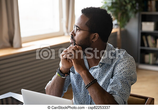 Guy sitting at table pondering over problem looking at distance - csp82253337