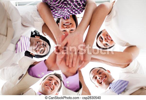 Lächelnde Geschäftsleute halten Händchen in einem Kreis - csp2830540