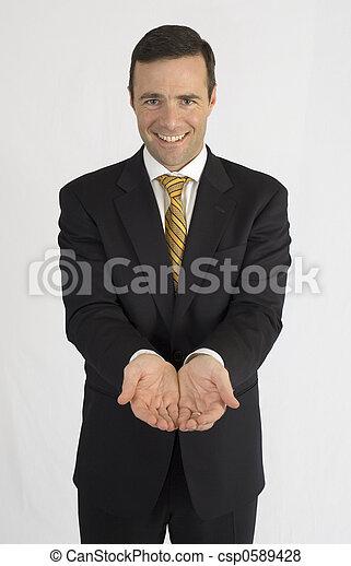 Ein Mann im schwarzen Anzug, der vor der Kamera Händchen hält - csp0589428