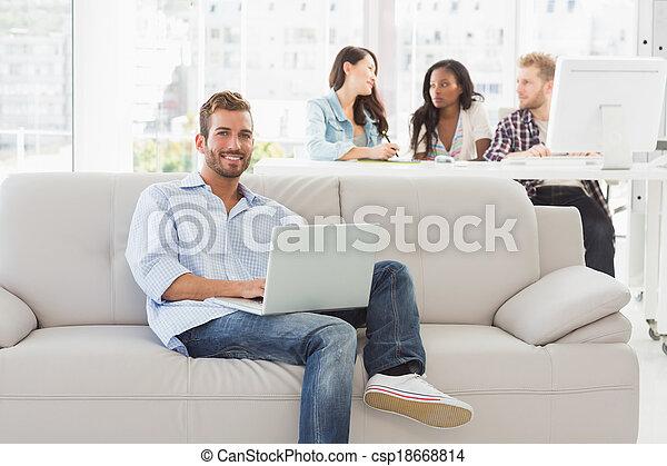 Un joven diseñador sonriente trabajando en H - csp18668814