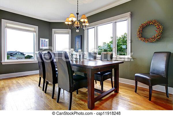 Un gran comedor verde con sillas de cuero y grandes ventanas. - csp11918248