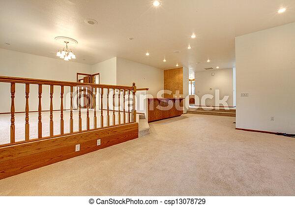 Una gran habitación vacía con alfombra beige y baranda. - csp13078729
