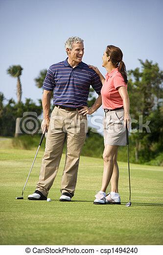 Una pareja hablando en el campo de golf - csp1494240