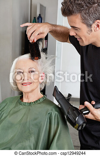 Hairdresser Blow Drying Woman's Hair - csp12949244