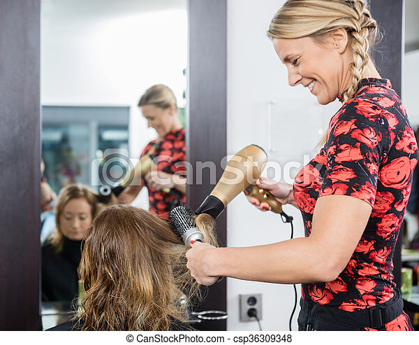 Hairdresser Styling Customer's Hair With Blow Dryer And Brush - csp36309348