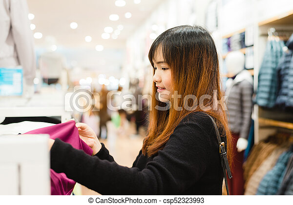 bf58b712eca Half body shot of a happy asian young woman with shoulder bag looking at  clothes hanging on the rail inside the clothing shop. shopping, fashion, ...