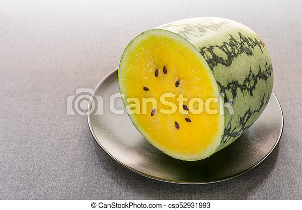 Half of yellow watermelon on black plate with gray tablecloth background. - csp52931993