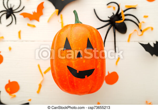 Halloween background with jack-o'-lanter, paper bats, spiders, confetti on white wooden background. Halloween holiday decorations. Flat lay, top view. Party invitation mockup, celebration. - csp73655213