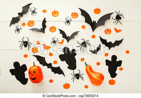 Halloween background with jack-o'-lanter, paper bats, spiders, confetti on white wooden background. Halloween holiday decorations. Flat lay, top view. Party invitation mockup, celebration. - csp73655214