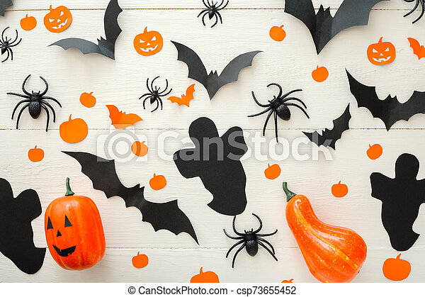 Halloween background with jack-o'-lanter, pumpkins, paper bats, spiders, confetti on white wooden background. Halloween holiday decorations. Flat lay, top view. Party invitation mockup, celebration. - csp73655452