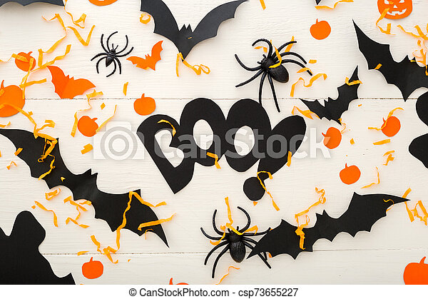 Halloween background with jack-o'-lanter, pumpkins, paper bats, spiders, confetti on white wooden background. Halloween holiday decorations. Flat lay, top view. Party invitation mockup, celebration. - csp73655227