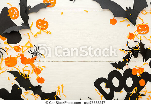 Halloween background with jack-o'-lanter, pumpkins, paper bats, spiders, confetti on white wooden background. Halloween holiday decorations. Flat lay, top view. Party invitation mockup, celebration. - csp73655247
