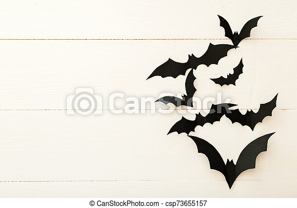 Halloween background with paper bats on white wooden background. Frame. Halloween holiday decorations. Flat lay, top view, copy space. Party invitation mockup, celebration. - csp73655157