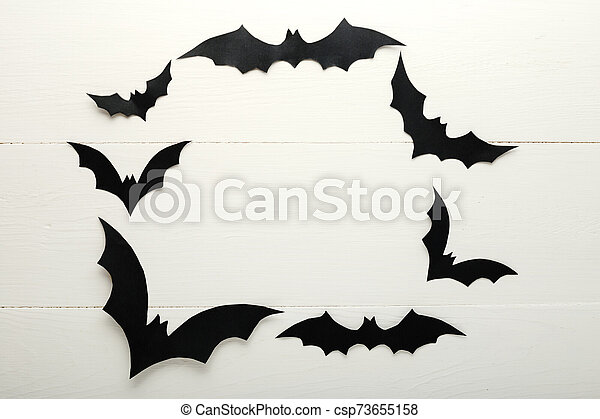 Halloween background with paper bats on white wooden background. Frame. Halloween holiday decorations. Flat lay, top view, copy space. Party invitation mockup, celebration. - csp73655158