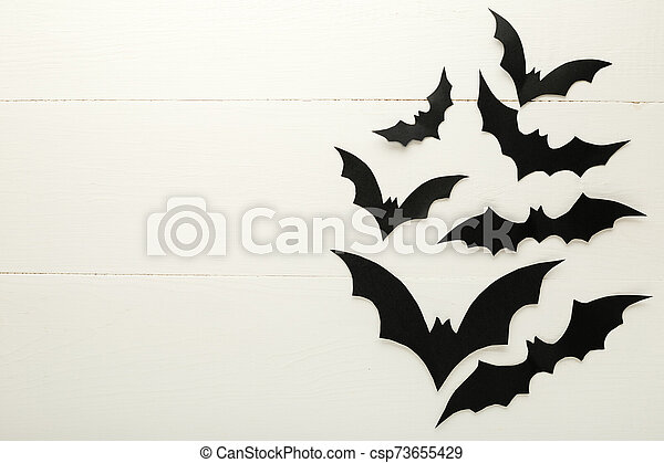 Halloween background with paper bats on white wooden background. Frame. Halloween holiday decorations. Flat lay, top view, copy space. Party invitation mockup, celebration. - csp73655429