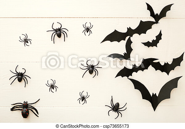 Halloween background with paper bats, spiders on white wooden background. Halloween holiday decorations. Flat lay, top view, copy space. Party invitation mockup, celebration. - csp73655173