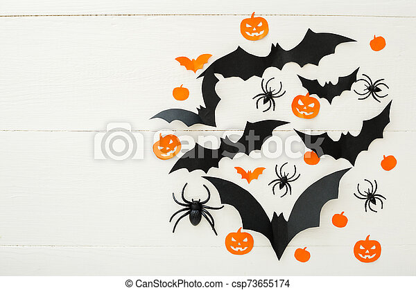 Halloween background with paper bats, pumpkins, spiders on white wooden background. Halloween holiday decorations. Flat lay, top view, copy space. Party invitation mockup, celebration. - csp73655174