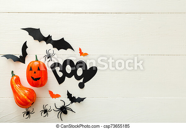 Halloween background with paper bats, spiders, jack-o'-lantern on white wooden background. Halloween holiday decorations. Flat lay, top view, copy space. Party invitation mockup, celebration. - csp73655185