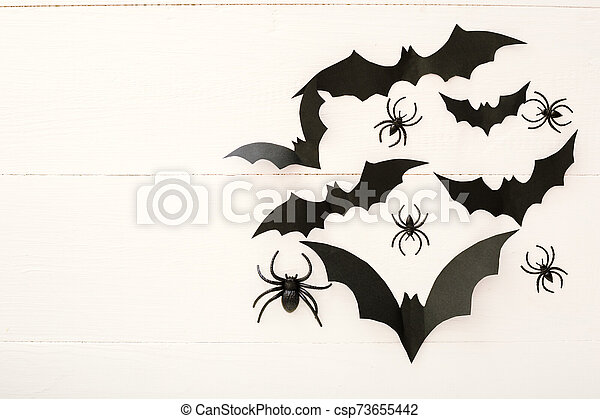 Halloween background with paper bats, spiders on white wooden background. Halloween holiday decorations. Flat lay, top view, copy space. Party invitation mockup, celebration. - csp73655442