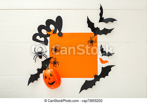 Halloween background with paper bats, spiders, jack-o'-lantern on white wooden background. Halloween holiday decorations. Flat lay, top view, copy space. Party invitation mockup, celebration. - csp73655202