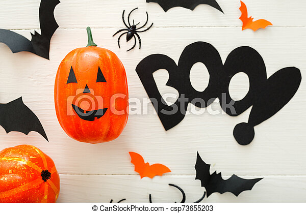 Halloween background with paper bats, spiders, jack-o'-lantern on white wooden background. Halloween holiday decorations. Flat lay, top view. Party invitation mockup, celebration. - csp73655203