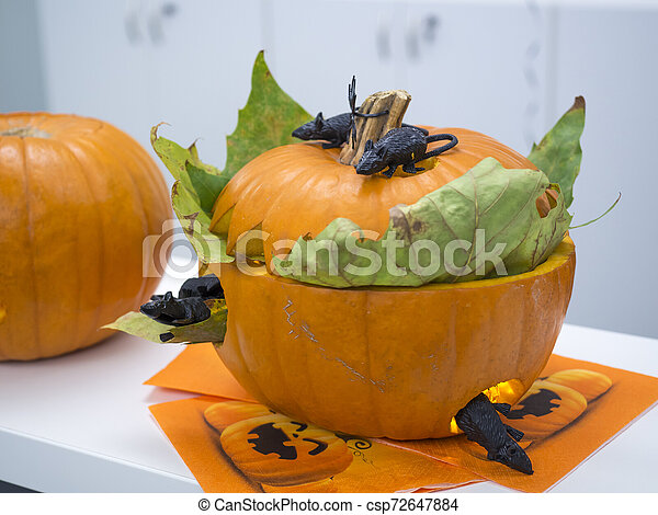 Halloween big orange pumpkin decorated with scary face. Jack O' Lantern on white table background - csp72647884