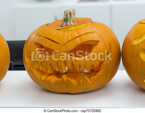 Halloween big orange pumpkin decorated with scary face. Jack O' Lantern on white table background - csp73725962