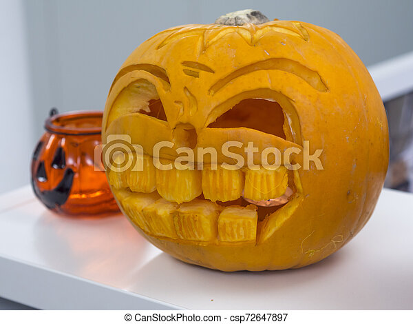 Halloween big orange pumpkin decorated with scary face. Jack O' Lantern on white table background - csp72647897