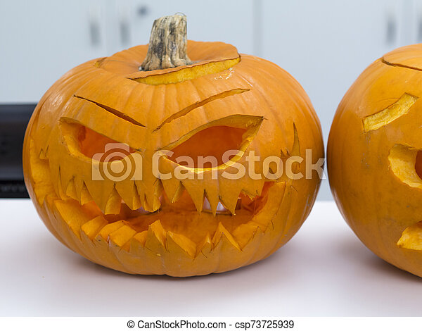 Halloween big orange pumpkin decorated with scary face. Jack O' Lantern on white table background - csp73725939