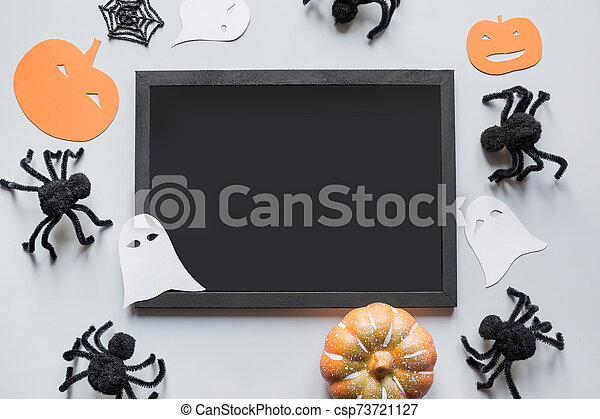 Halloween blank with space for text and party decor, black spiders, pumpkin, white ghost on grey. Flat lay, top view, copy space. - csp73721127
