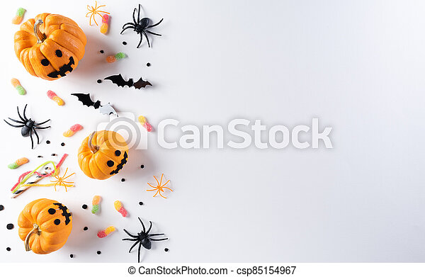 Halloween decorations made from pumpkin, paper bats and black spider on white background. Flat lay, top view with copy space for text. - csp85154967