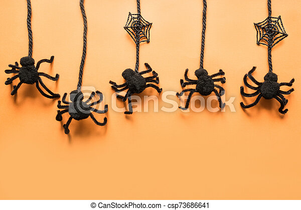 Halloween decorations with black spiders on orange background. Flat lay, top view, copy space. - csp73686641