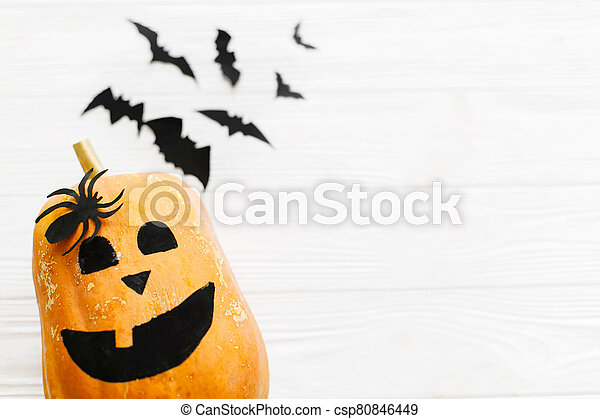 Halloween flat lay. Jack o lantern pumpkin and black bats, ghost, spider on white wooden background, copy space. Modern halloween decorations. Minimalistic flat lay - csp80846449