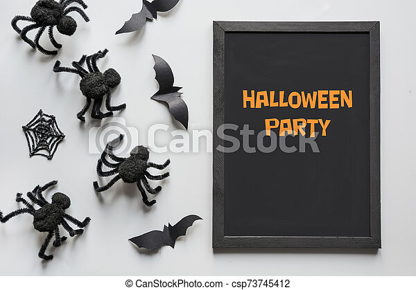 Halloween invitation with black spiders on grey. Flat lay, top view, copy space. Party accessories. Happy halloween concept. - csp73745412