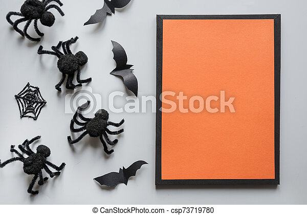 Halloween invitation with black spiders, bat on grey. Flat lay, top view, copy space. Party accessories. Happy halloween concept. - csp73719780
