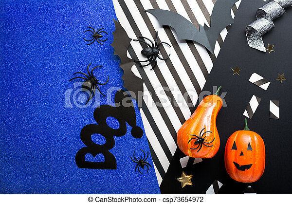 Halloween party invitation mockup, celebration. Halloween decorations concept with bats, spiders, jack-o'-lantern, stars, confetti, ribbon. Flat lay, top view, copy space on black, white and blue background. - csp73654972