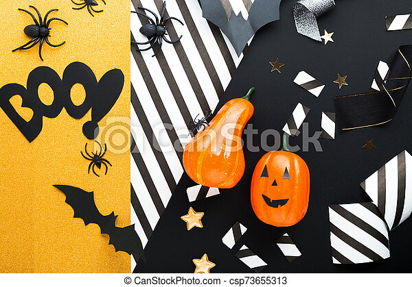 Halloween party invitation mockup, celebration. Halloween decorations concept with bats, spiders, jack-o'-lantern, stars, confetti, ribbon. Flat lay, top view, copy space on black and white background. - csp73655313