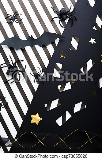 Halloween party invitation mockup, celebration. Halloween decorations concept with bats, spiders, jack-o'-lantern, stars, confetti, ribbon. Flat lay, top view, copy space on black and white background. - csp73655026