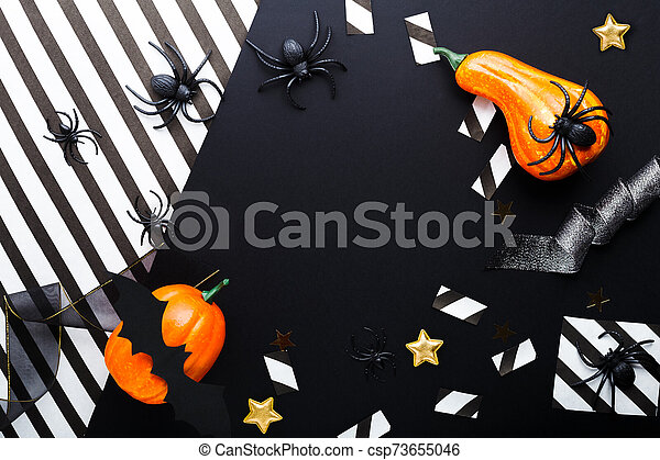 Halloween party invitation mockup, celebration. Frame. Halloween decorations concept with bats, spiders, jack-o'-lantern, stars, confetti, ribbon. Flat lay, top view, copy space on black and white background. - csp73655046